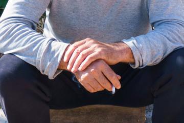 Men's hands with a cigarette close-up