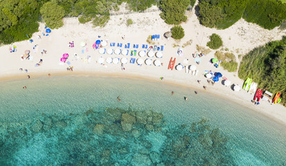Fototapete - View from above, stunning aerial view of a beautiful beach full of colored beach umbrellas and people swimming in a turquoise clear water. Capriccioli Beach, Costa Smeralda, Sardinia, Italy.