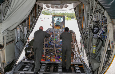 U.S. Coast Guardsmen unload relief supplies for Hurricane Dorian victims from their C-130 aircraft  in Andros