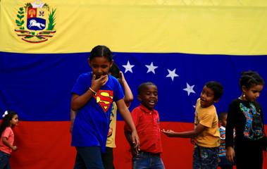 Children play in front of the Venezuela flag in Caracas