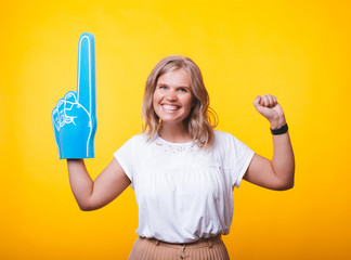 Photo of cheerful woman, with big finger glove, supporter, over yellow wall