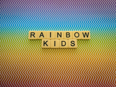 """Bright rainbow zig zag pattern background sign with the words """"RAINBOW KIDS"""" in text lettering, for a brilliant and eye catching sign or banner"""