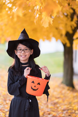 Portrait of little asian girl in witch costume with pumpkin for halloween celebration