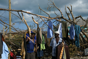 Men work to salvage some of their damaged clothes in a destroyed neighborhood in the wake of Hurricane Dorian in Marsh Harbour