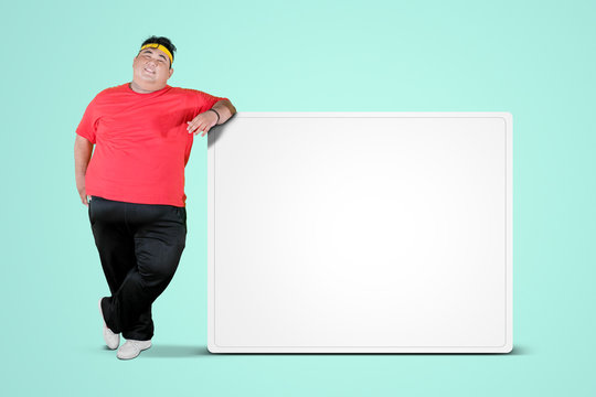 Overweight man leaning on a blank whiteboard