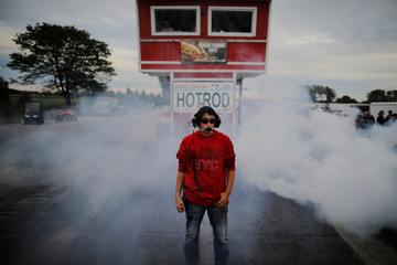 Hunter Dye stands amid smoke from tires in the water box at the starting line at the Great Lakes Dragway in Union Grove