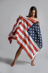 Beautiful woman wrapped in American flag on grey background. American Partiot Sexy Girl with USA flag