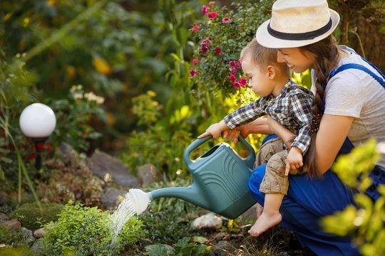 woman gardener and son watering garden