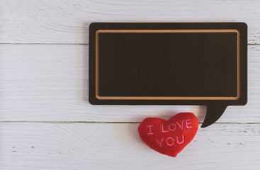 """Flat lay of black blank speech bubble wooden sign on white marble background with red heart """"I LOVE YOU"""". Concept of couple, family, friend, lover and Valentine. Love photo frame"""