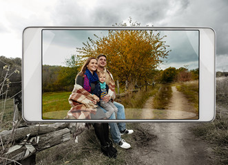 Smartphone displaying photo of cute loving family with little son in autumn park