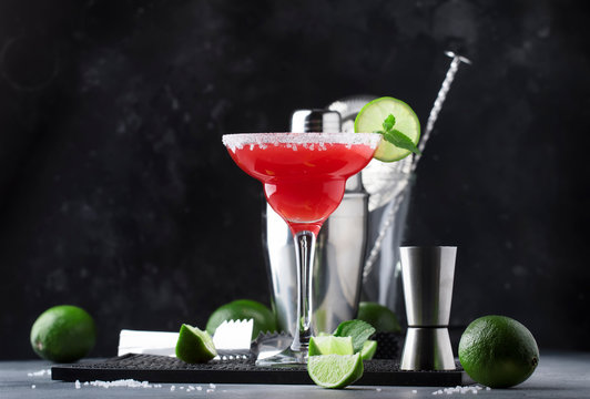 Watermelon margarita, alcoholic cocktail with silver tequila, lime juice, mint, watermelon and crushed ice, metal bar tools, gray background