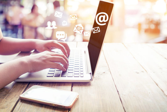 Hand of female using laptop computer sending e-mail message with email address symbol and envelope icon. Online marketing concept.