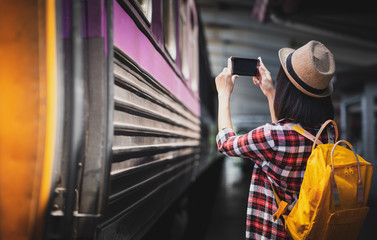 Tourist woman taking a photo with smartphone of side of train on railway background. Young asian woman traveler with backpack in the railway, Travel concept