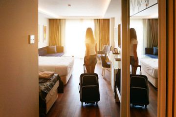 A girl comes into a bright hotel room with a suitcase on wheels. Check in at the hotel. Wall mural