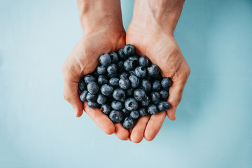 Closeup man holds blueberries in hands on a blue background. Source of vitamins and diet food or...