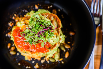 A dish of vegetable patties, Halloumi and Avocado, stacked up on a dark blue plate.