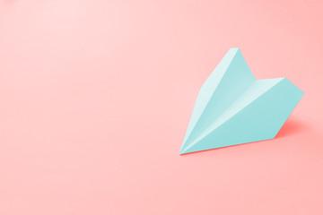 pale blue paper plane on a coral background. trendy 2019 color concept