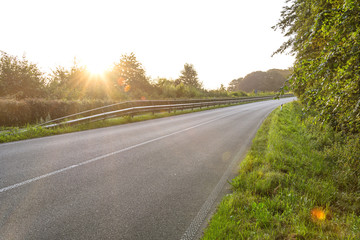 Scenic country road at sunrise with lens flare