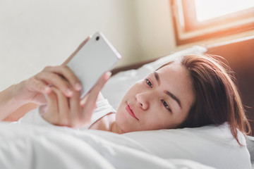 Smile young asian woman playing with her smathphone on white pillow on bed in bedroom on morning time after wake up, Selective focus.