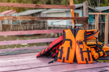orange life jackets on pink wood with Fishing village background, copy space.