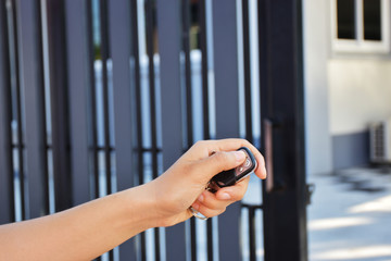 left hand press remote control for open or close the gate. Background is blurred gate and home. Lock or unlock by remote key.