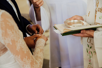 the young couple puts on rings during the wedding