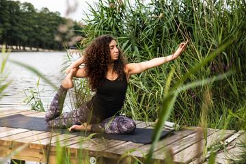 Medytacja nad jeziorem. Młoda joginka ćwiczy na macie jogę. Pozycja jogi. Joga nad brzegiem jeziora.