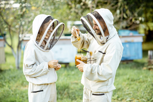Two beekepers in protective uniform standing together with honey in the jar, tasting fresh product on the apiary outdoors