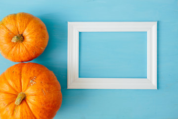 Orange pumpkins with white frame for picture on blue wooden background Thanksgiving and Halloween concept. View from above. Top view. Copy space for text and design
