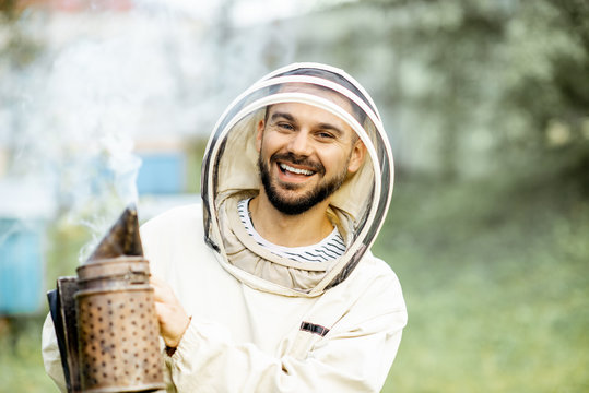 Portrait of a cheerful beekeeper in protective uniform with bee smoker on the apiary