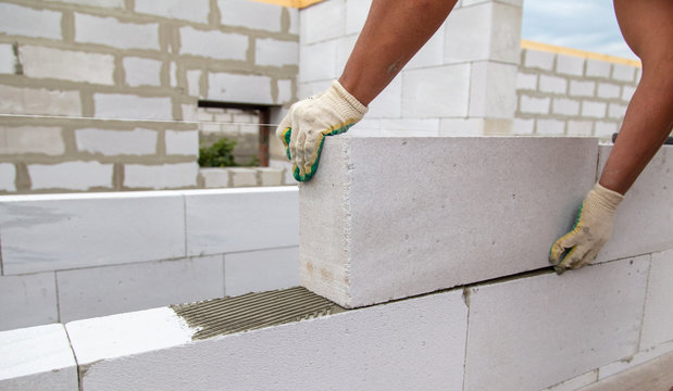 A worker lays foam concrete bricks in a house under construction