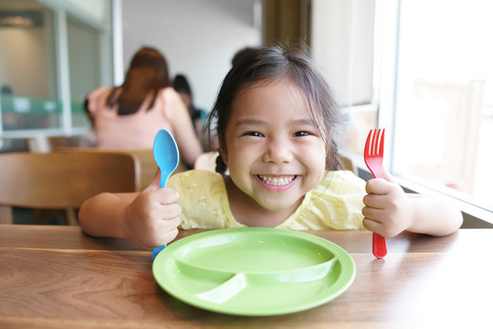 Asian child cute hungry or kid girl holding colorful spoon and fork with dish for wait eat delicious food with smiling and happy for enjoy lunch or breakfast in morning at restaurant or food court