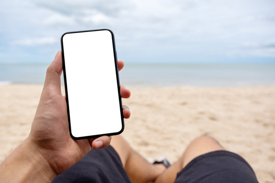 Mockup image of a man's hand holding black mobile phone with blank desktop screen while laying down on beach chair