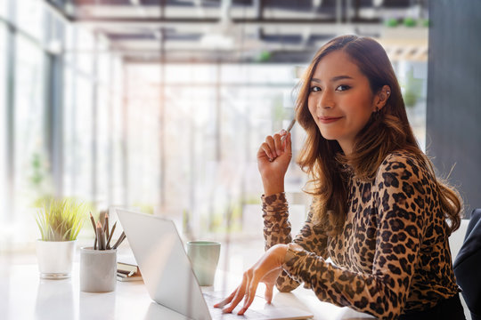 Confident asian businesswoman smiling and look at camera while working on laptop at modern office. Woman laptop working concept