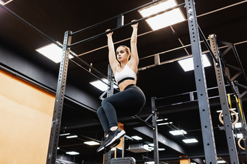 Bottom view - a strong athletic young champion woman works with her own weight on the bar. The concept of building a slim body