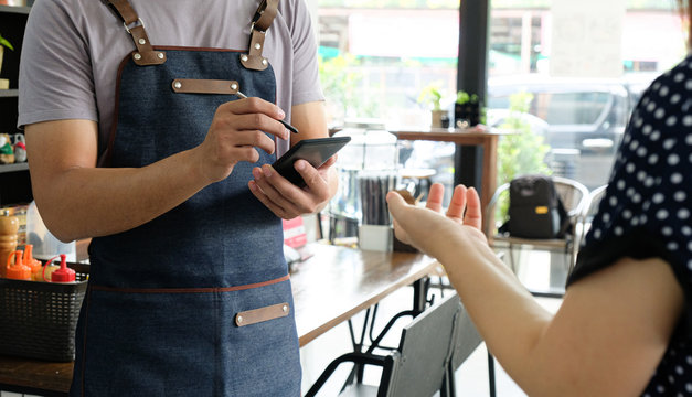 Employee holding a smartphone to save the menu the customer order.
