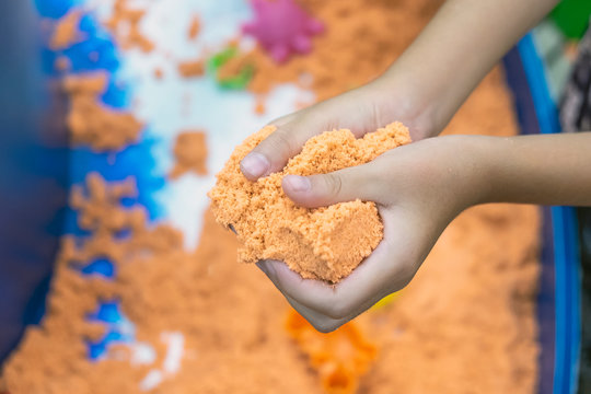 The hand of a child playing in the sandbox