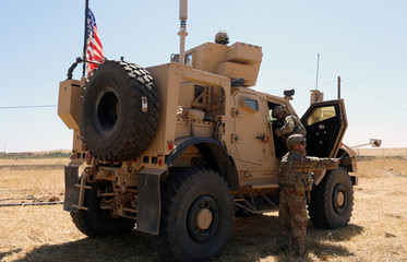 An American flag flutters on a U.S military vehicle during a joint U.S.-Turkey patrol, near Tel Abyad