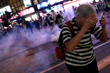 A woman runs away from tear gas after a march to call for the passing of the proposed Hong Kong Human Rights and Democracy Act by the U.S. Congress, in Hong Kong