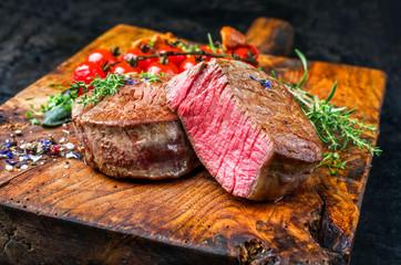 Gebratene dry aged Rinderfilet Steak Medallions natur mit Tomaten und Pfifferlinge als closeup auf einem rustikalen Holz Schneidebrett