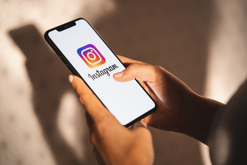 BERLIN, GERMANY JULY 2019: Woman hand holding iphone Xs with logo of instagram application. Instagram is largest and most popular photograph social networking.