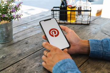 BERLIN, GERMANY JULY 2019: Woman hand holding iphone Xs with logo of Pinterest application in a restaurant. Pinterest is an online pinboard that allows people to pin their interesting things.