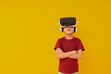 Young Asian girl with virtual reality glasses, kid wow and exiting with VR presentation on yellow...
