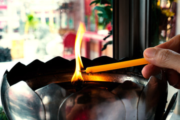 Faith and religious.Man hand holding yellow candle getting fire  from big oil lamp in chinese shrine.