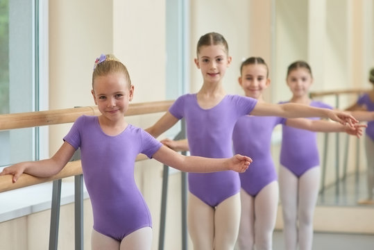 Young ballerinas standing near ballet barre. Group of young ballet dancers in purple leotards at the ballet barre. Lesson of ballet dance.