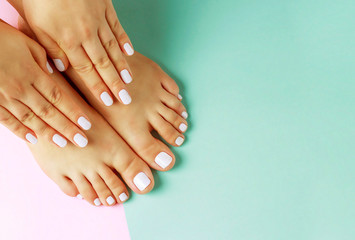 Photo sur cadre textile Pedicure Female hands with white manicure and pedicure on a pink and blue background, top view