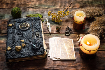 Tarot cards and a book of magic on the table. Wall mural
