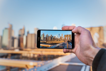 smartphone taking a picture of the skyline of new york from the brooklyn bridge