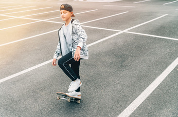 Teenager skateboarder boy with a skateboard on asphalt playground doing tricks. Youth generation Freetime spending concept image.