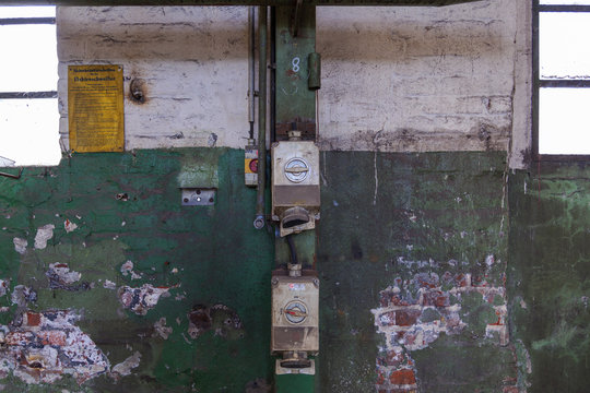 Front view of electric meter, Circuit Breaker and Electric wires system on rough old scratch painted with white and green brick wall in abandon industrial building.